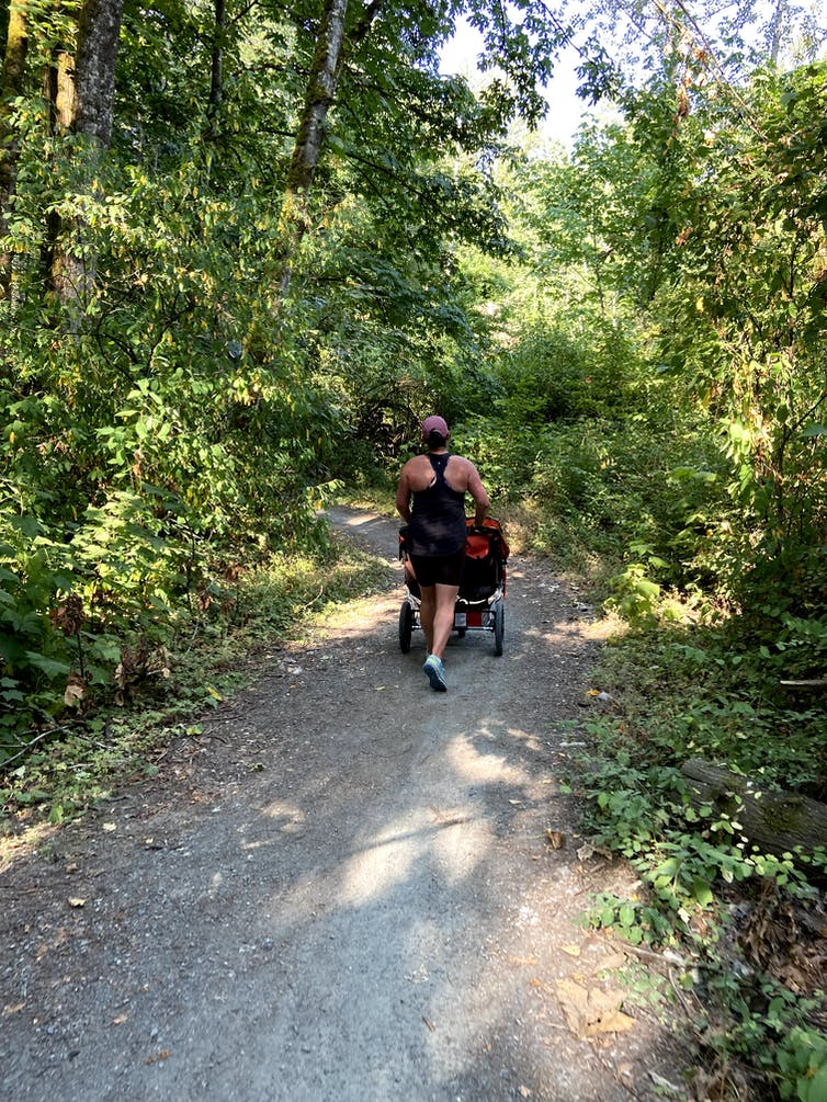 A woman seen from behind, jogging on a wooded path while pushing a double stroller
