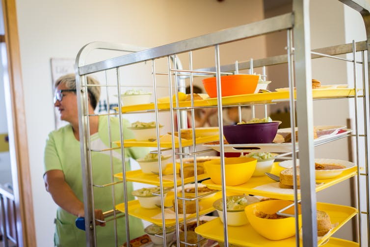 Person in scrubs wheeling bowls of food in stacked on a cart in a nursing home.