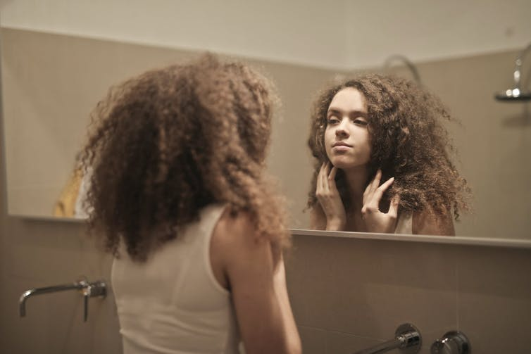 Woman in white tank top looking at herself in the mirror.