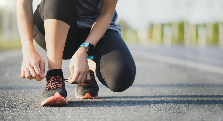 A woman lacing her shoes ahead of going for a run.