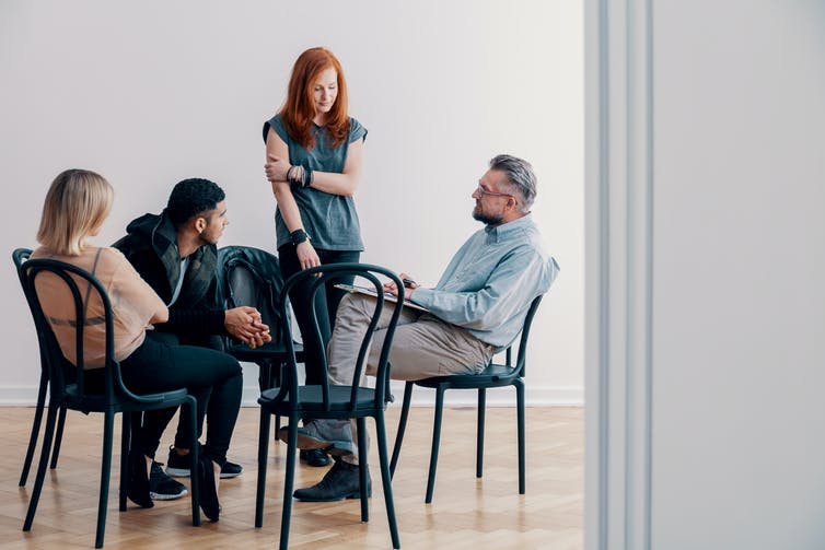A group therapy session. One woman is standing and addressing three others.