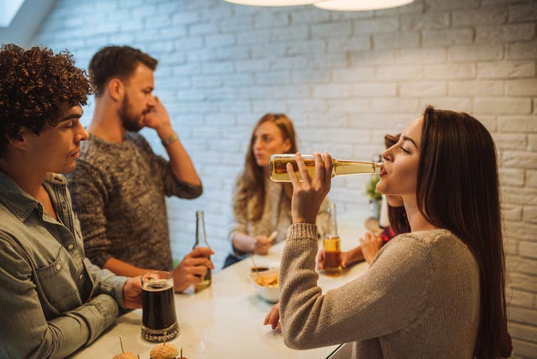 Person drinking alcohol with friends