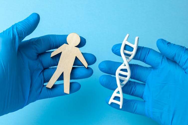 A lab working wearing blue gloves holds a paper cutout of a person in one hand, and a paper DNA helix in the other.
