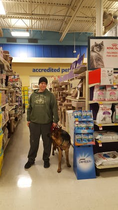 A war veteran with a service dog, in a supermarket aisle