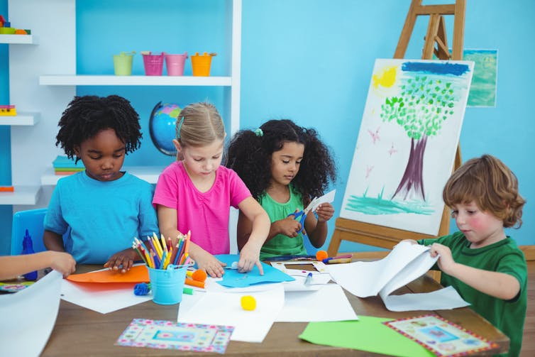 Four children painting and drawing.