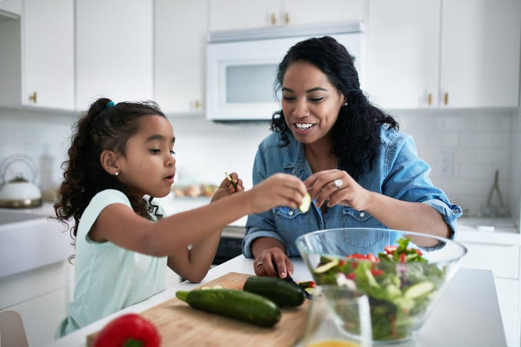 girl and woman prepare vegetables together