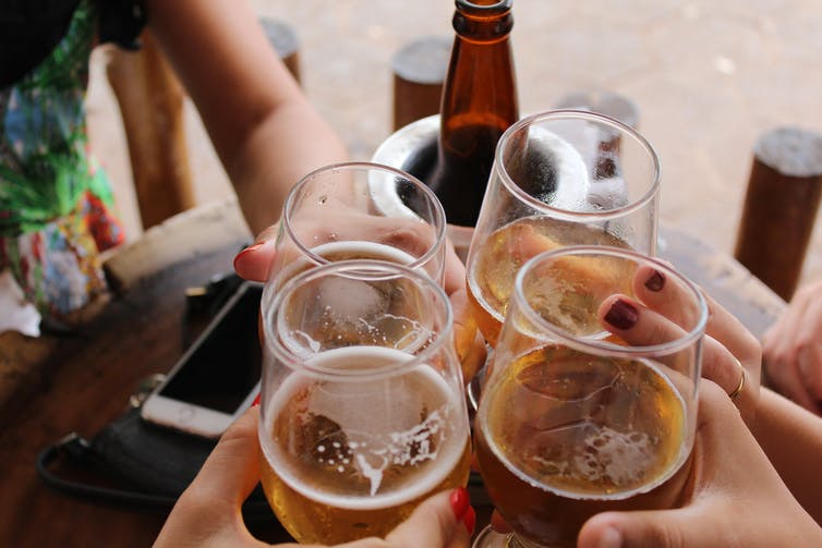 Four people toasting their beer glasses.