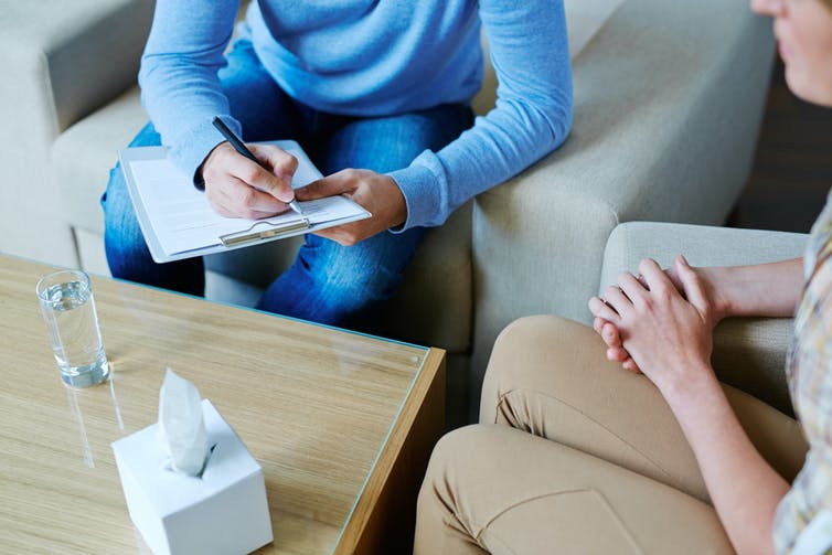 A therapist takes notes while talking to their patient.