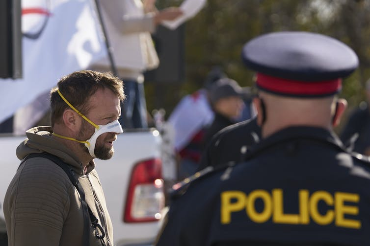 A police officer seen from the back in foreground with an anti-mask protester in the background