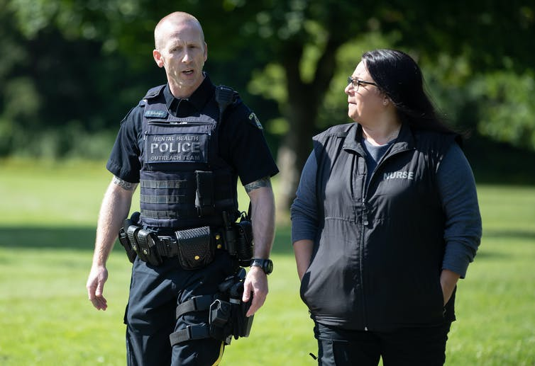 A police officer in full uniform walks with a dark-haired woman in a park with trees in the background.