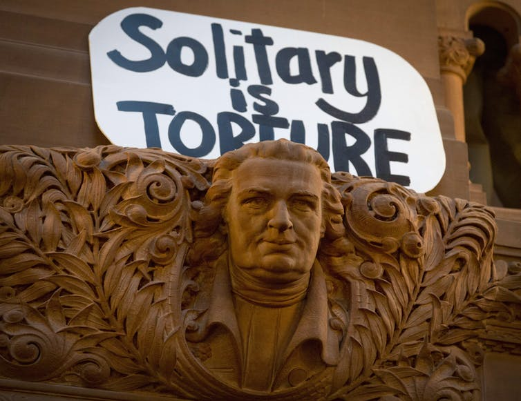 Protest sign saying 'solitary is torture' displayed at the New York State Assembly's Great Western Staircase