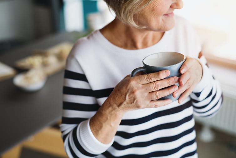 A woman in a striped jumper holds a mug.