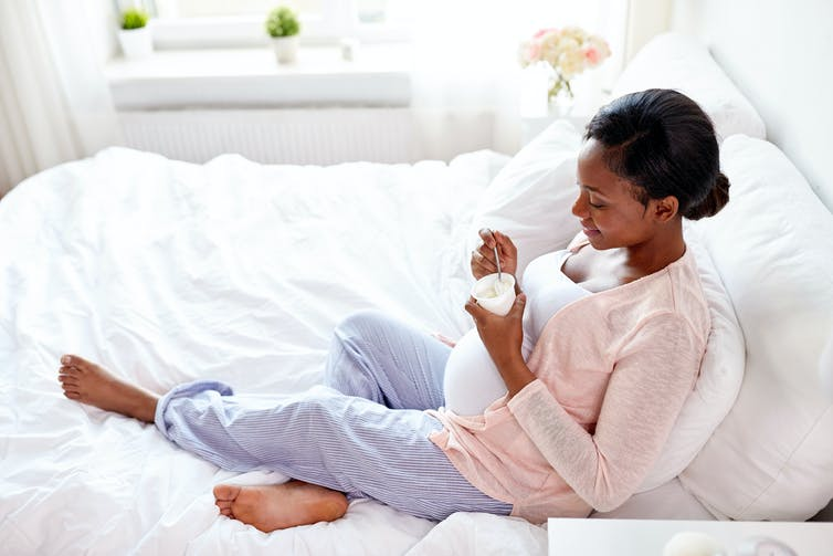 Happy pregnant woman eating yogurt in bed at home.