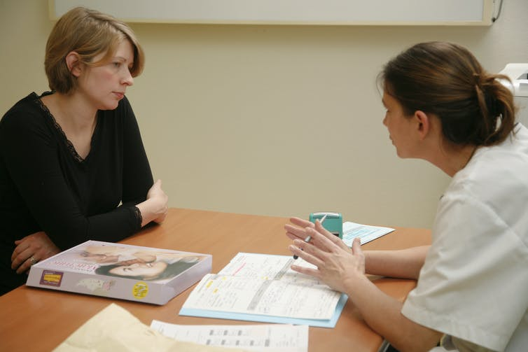 A pregnant woman talking to a health care provider.