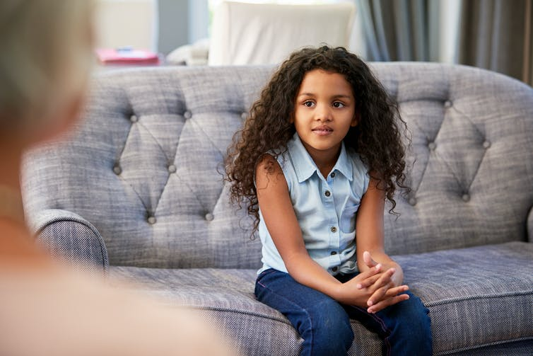 A young girl sits on a couch, appears to be talking with a therapist.