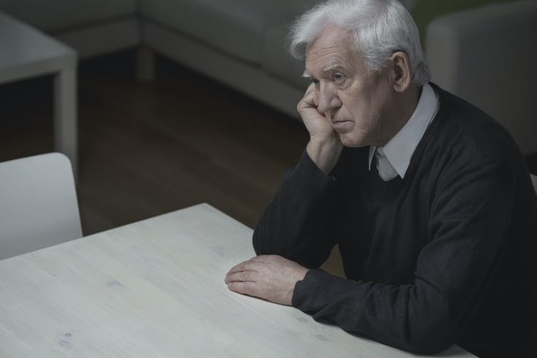 Elderly man sitting at a table, looking tired and depressed.