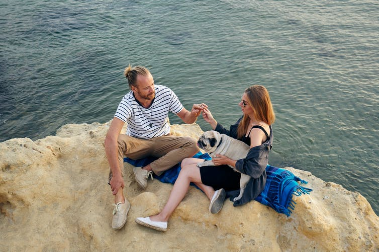 A man and a woman chill on a rock by a lake while smoking a joint. The woman holds a pug on her lap