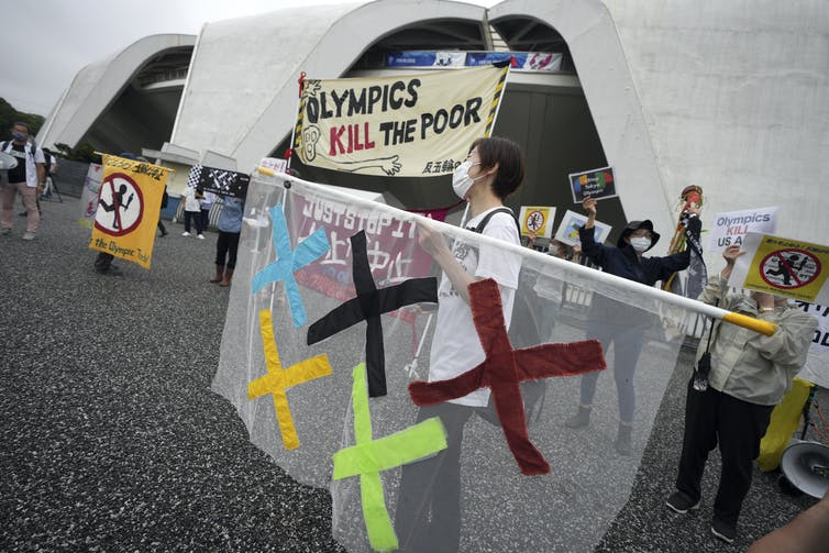 Protester holding a sign that says 'Olympics kill the poor.'