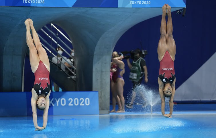 Two divers are about to enter the water simultaneously.