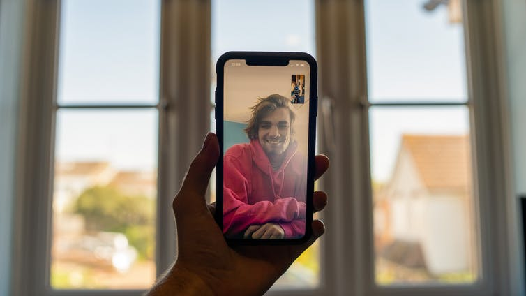 A hand holds up a smartphone on a video call.