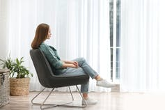 Woman in casual clothes sitting in a chair near a window