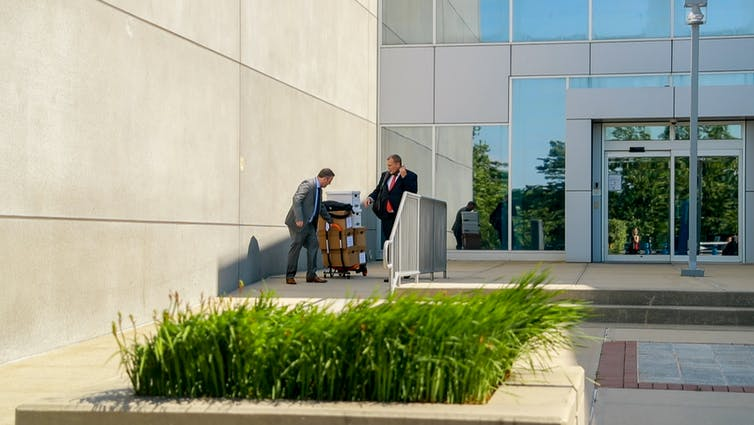 Men in suits move large boxes of documents around outside a courthouse.