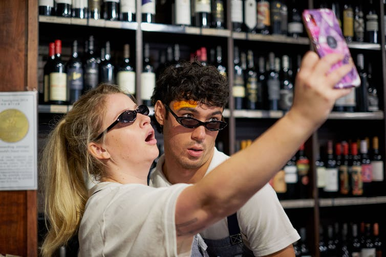 A man and a woman pose for a selfie in a bottle shop, both wearing pointy sunglasses