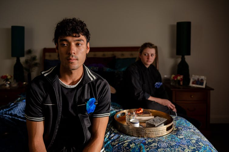 A man sits on the edge of a bed looking ahead with a serious expression. Behind him, a woman sits in the shadows