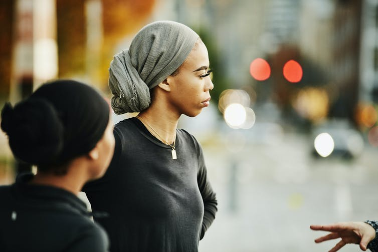 Two people wearing headscarves looking at another person out of frame standing on a blurred out street.